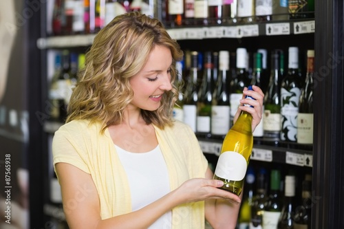 Photo  Smiling pretty blonde woman showing a wine bottle