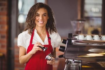 A smiling barista pressing coffee