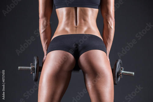Fototapeta young girl with dumbbells and taut buttocks