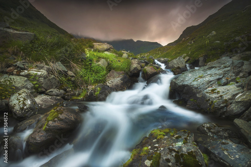 Foto op Aluminium Bos rivier Waterfall up in the mountains during sunset