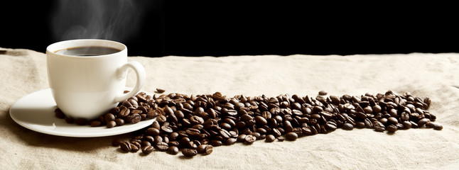 Fototapeta Kawa Panoramic view of frothy coffee cup with beans on fabric flax