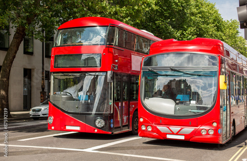 city street with red double decker buses in london