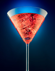 Obraz na Szkle Glass of red martini on a beautifully shining on a blue background