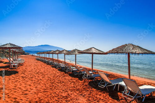 Valokuvatapetti Straw umbrellas and sunbeds on a red sand beach and turquoise water