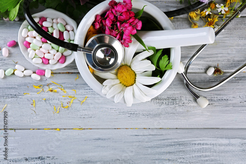 Photo  Alternative medicine herbs, berries and stethoscope on wooden table background