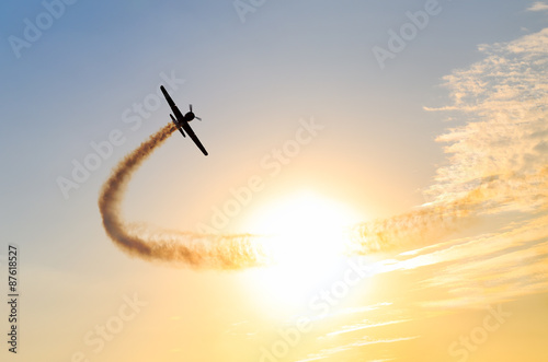 Fotografija  Silhouette of an airplane performing flight at airshow at sundown