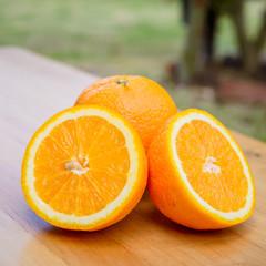 Slice of orange on wooden table.