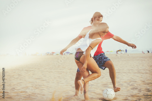 Young couple playing football on the beach with analog film effe