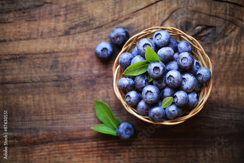Fotografía  Fresh ripe garden blueberries in a wicker bowl on dark rustic wooden table