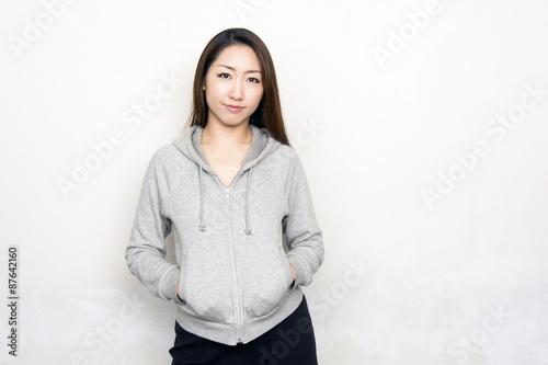 Fotografie, Obraz  パーカーを着て壁際に立つ女性