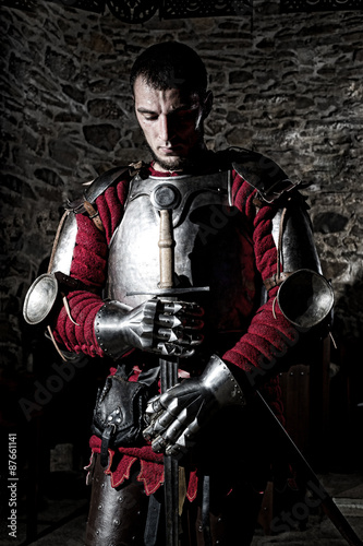 Photo  Knight Standing With Head Bowed in Prayer and Metal Sword