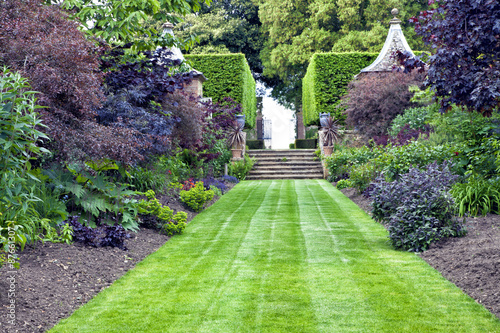 Fotobehang Tuin Grass path leading to stone stairs in a landscaped garden