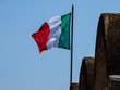 Italian flag on the background of pure Roman sky, Roma, Italy