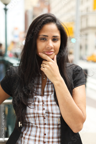 Fotografie, Obraz  A woman on a Manhattan street looks at viewer with her hand to her chin