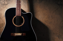 Black Acoustic Guitar On The Old Dirty Wall, With Shadow