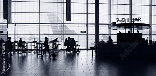 Poster Aeroport Airport interior with food bar and tourists.