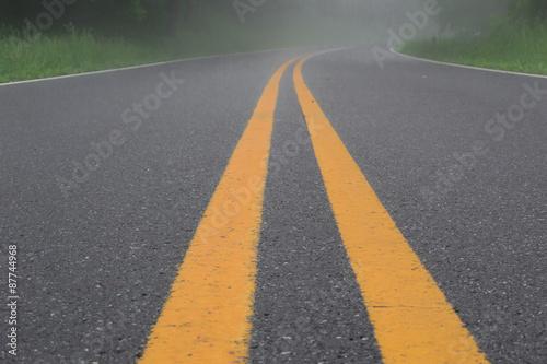 podwojne-zolte-linie-na-drodze-we-mgle