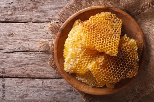 Golden honeycombs on a wooden plate. Horizontal top view Wallpaper Mural
