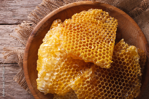 Golden honeycombs on a wooden plate Wallpaper Mural