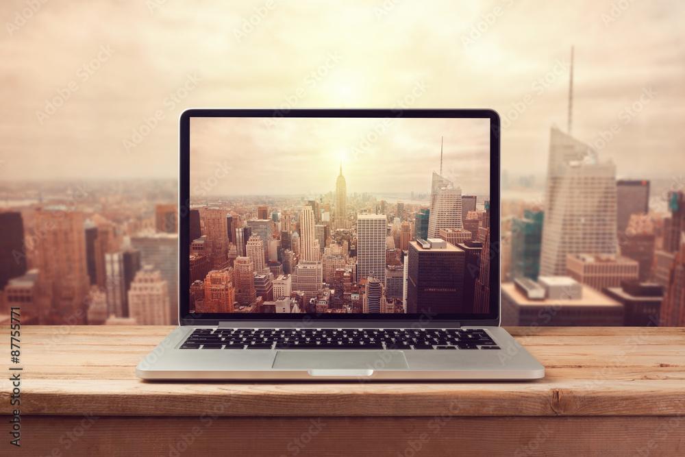 Fototapeta Laptop computer over New York city skyline. Retro filter effect