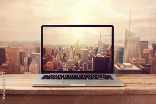 Fotografía  Laptop computer over New York city skyline. Retro filter effect