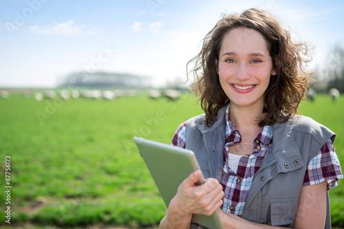 Young attractive farmer in a field using tablet Billede på lærred