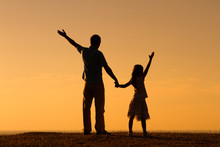 Father And Daughter Gretting The Sunset