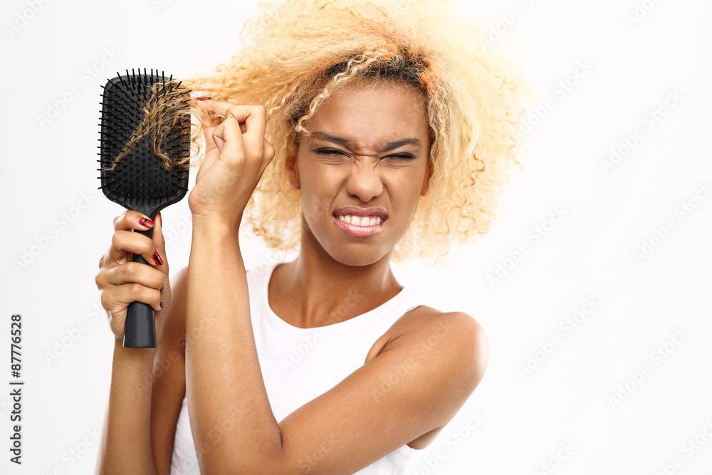 Fototapeta  Splątane włosy. Ciemnoskóra młoda kobieta rozczesuje włosy szczotką