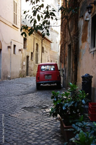 The narrow romantic Roman street and the old red car