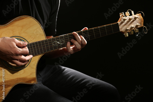 Papiers peints Musique Young man playing on acoustic guitar on dark background