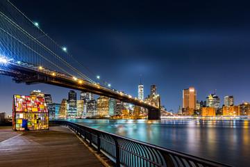 Brooklyn Bridge and the Lower Manhattan skyline by night as viewed from  Brooklyn Bridge Park in New York City