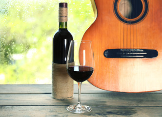 FototapetaAcoustic guitar and glass of wine next the window with rain drops