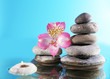 Stack of spa stones with flower and candlelight on blue background