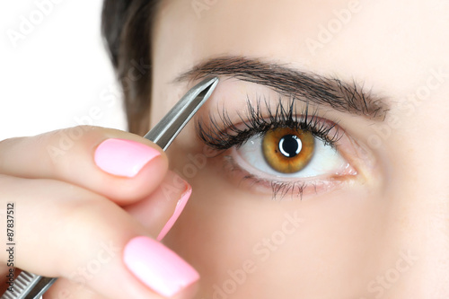 Young woman plucking eyebrows with tweezers close up Canvas Print