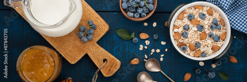 A healthy breakfast on a dark blue wooden background: Oatmeal, milk, blueberries, honey and almonds. Rustic style.