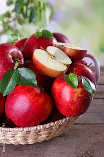 Tuinposter Bier / Cider Red apple in wicker basket on wooden table, closeup