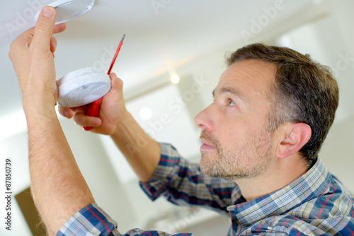 Fotobehang Rook Man installing a smoke alarm