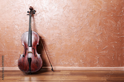 Tableau sur Toile Classical cello and bow on brown wall background