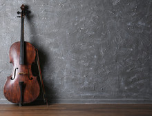 Classical Cello And Bow On Gray Wall Background