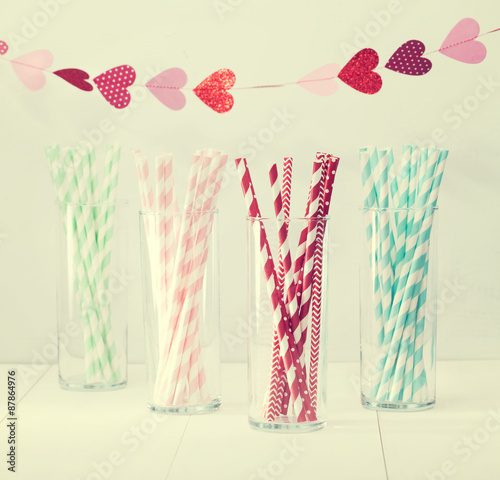 Fotografia  Colorful paper straws with a garland of hearts
