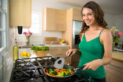 Poster Cuisine Woman home chef single portrait cooking vegetables vegan meal on stove grill