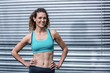 Smiling muscular woman with hands on hips