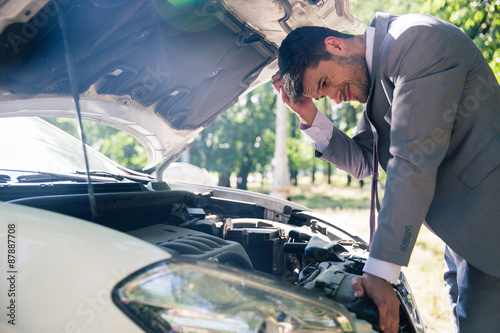 Fotografía  Man looking under the hood of car