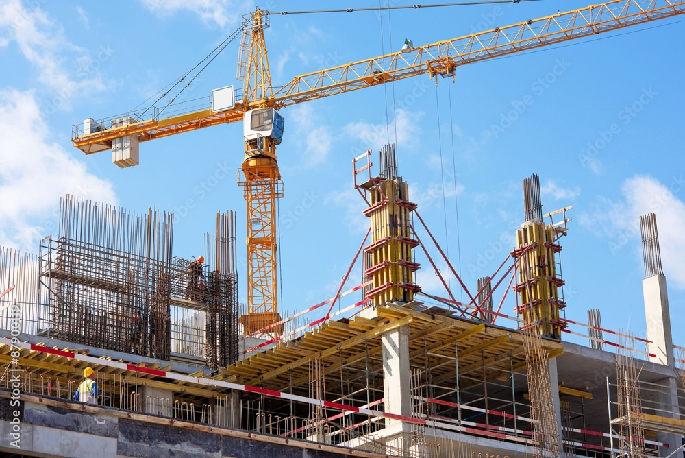 Fototapeta A New building is being constructed with use of tower crane