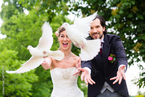 Fotografía  Pareja de novios con vuelan palomas blancas en la boda