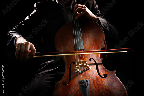 Fotografía Man playing on cello on dark background