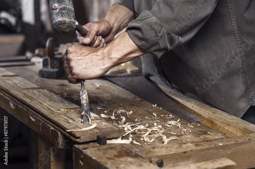 Slika na platnu Carpenter with a hammer and chisel