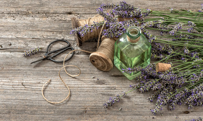 Lavender oil with fresh flowers and scissors on wooden backgroun