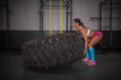Fit and strong girl exercise with big tire.