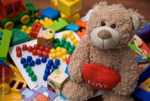 obraz PCV miś otoczony plastikowych zabawek